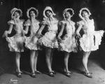 Chorus girls in ruffled dresses and bonnets