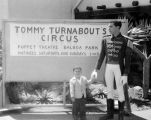 Gale Todd as ringmaster standing next to a sign announcing Tommy Turnabout's Circus at the Puppet...