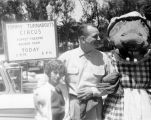 Comm. Hetler and Judy, with Hepzibah Hippopotamus, near a sign announcing Tommy Turnabout's Circus...