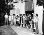 Harry Burnett directs a group of children presenting the marionettes they have made at Idyllwild. ...