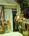 Harry Burnett standing outside his workshop on Oakshire Drive.  Many puppets are displayed nearby.