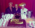 Forman Brown, Richard Brandon and Harry Burnett pose behind a cake decorated for the 50th...