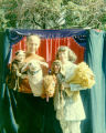 Puppeteers holding puppets in front of a puppet stage at a Los Angeles  Guild of Puppetry party. ...