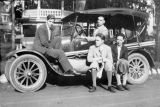 The Yale Puppeteers sitting on a car.