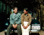 Richard Brandon and Socorro sitting on a car bearing a 1940 Michigan license plate mounted on a...