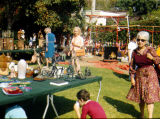 People looking at items for sale at the puppet yard sale.