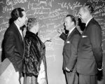 Harry Burnett and Forman Brown watch as singer and entertainer Spade Cooley signs the autograph...