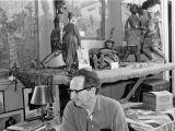 Harry Burnett sitting in front of an exhibit of Sicilian marionettes in the 1960s.