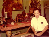 Harry Burnett sitting in front of an exhibit of Sicilian marionettes.