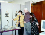 Library staff members Carol Baldwin and Elia Rocha show Michael Bridges, estate executor, the work...