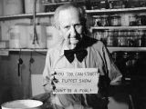 Harry Burnett in his retirement years in his workshop at Turnabout House, holding a sign,...