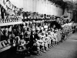 Puppeteer Harry Burnett in his workshop surrounded by numerous marionettes.  A sign reads,...