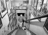 Harry Burnett standing on the stairway at Turnabout House, the residence of the Yale Puppeteers. ...