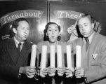 Turnabouters Harry Burnett, Dorothy Neumann and Forman Brown blow out candles at the door to...