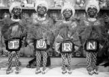 Four Voodoo Chorus dancer puppets, each bearing one letter of T-U-R-N under their skirts in...