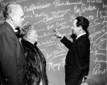 Forman Brown and Harry Burnett and unknown woman looking at the autograph wall at Turnabout...