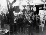 A group of children in the patio of Turnabout Theatre.  Balloons are hung, and someone is in clown...