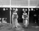 Two clowns in the patio of Turnabout Theatre, where balloon have been hung.