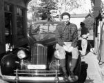 Harry Burnett sitting on the fender of a car in a gas station in Solvang in 1947.