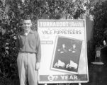 Arthur Cathey standing next to a Turnabout Theatre billboard in 1947, its 6th year.