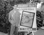 Sid Krofft, a puppeteer with Turnabout Theatre, standing next to a theater billboard in 1947, its...