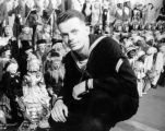 Friend James Rasmussen in Navy uniform, kneeling near Harry Burnett's puppets at Turnabout Theatre...