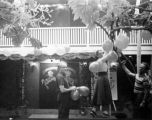 Forman Brown, Dorothy Neumann and another man decorate the Turnabout Theatre patio with balloons...